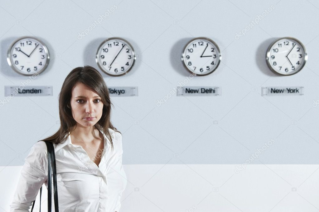 Portrait of young businesswoman standing with world time zone clocks in background — Stock Photo #10951269