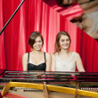 Pretty girls play two part harmony on a piano — Stock Photo