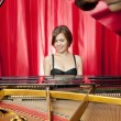 Pretty young woman playing a grand piano - Stock Photo