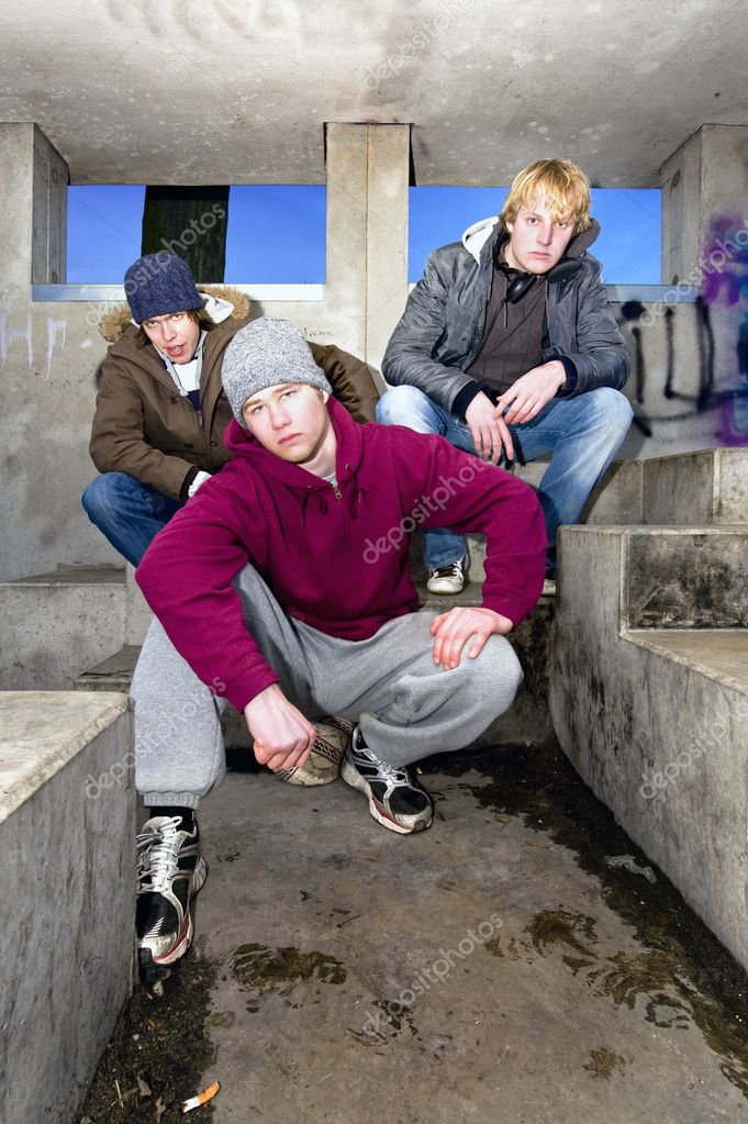 Three angry looking gangmembers in a dirty, concrete bunker at dusk. — Stock Photo #11863505