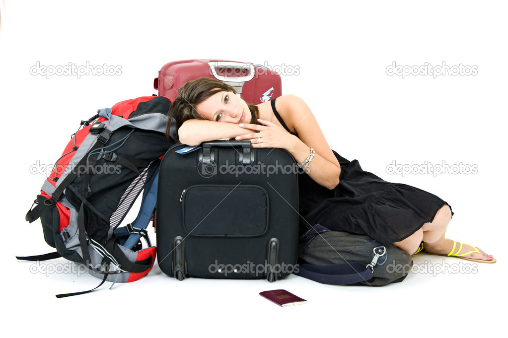 Young woman resting on her luggage, weary from travelling  Stock Photo #11869030