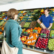 Greengrocer serving a customer — Stock Photo
