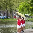 Oarsmen carrying a rowing boat — Stock Photo #11895316