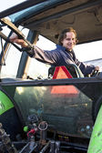 Farm hand in a tractor — Foto Stock