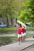 Oarsmen carrying a rowing boat — Stock Photo