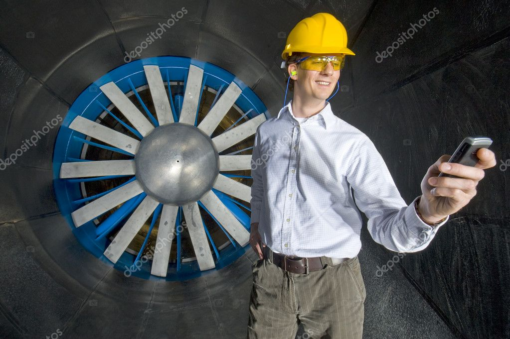 A smiling engineer, looking at his phone inside the realms of an industrial windtunnel — Stock Photo #11970888