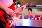 A live performance of a guitarist on stage playing together with a deejay. Viewed from the stage. — Stock Photo