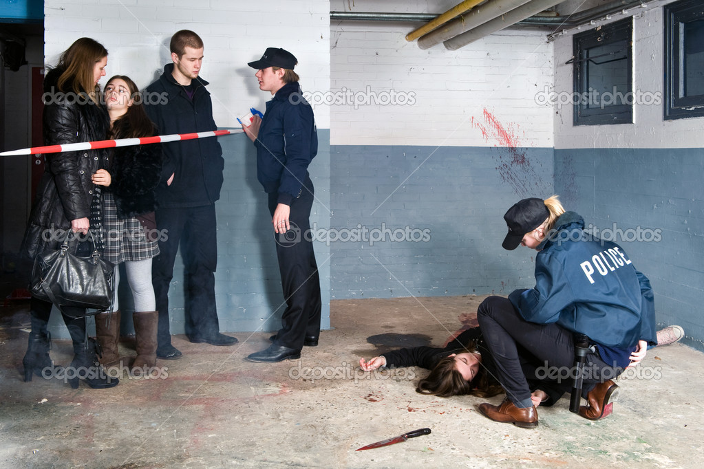 Bystanders being held at a distance by a police man at a murder scene, with a police woman tending to the victim — Stock Photo #11980783