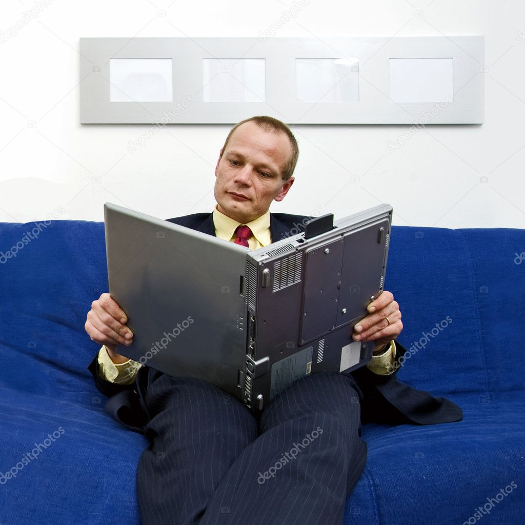 Man wearing a suit, reading an e-book, holding his laptop rotated, as if a real book — Stock Photo #11982751