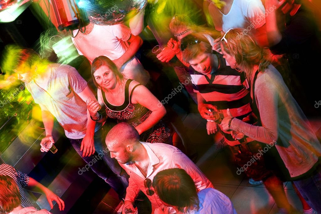 Girl smiling at the camera on a crowdy dance floor in a discotheque  Foto de Stock   #11983795