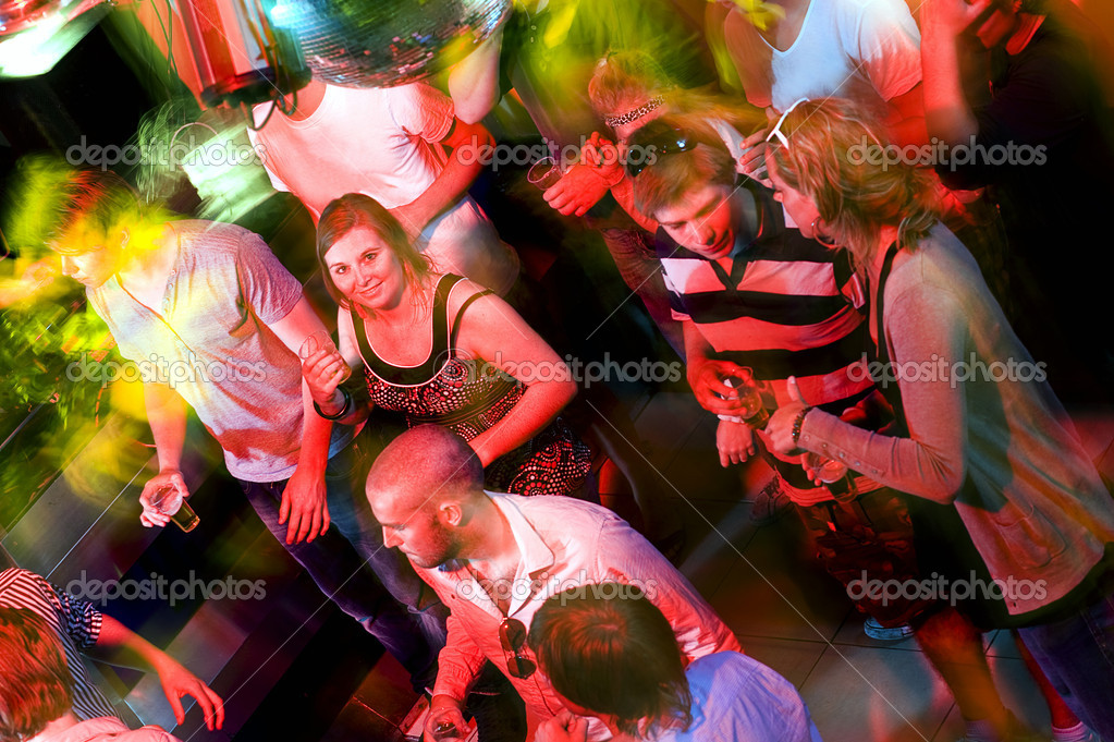Girl smiling at the camera on a crowdy dance floor in a discotheque — Stock Photo #11983795