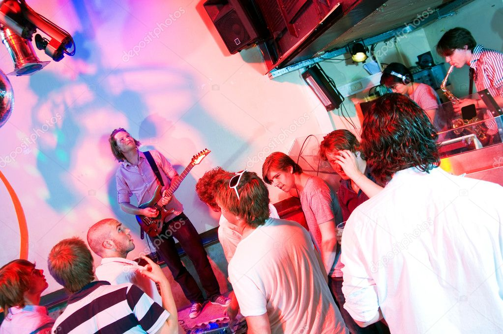 Guitarist on stage in a nightclub, with party crowd, saxophonist and DJ — Stock Photo #11983962