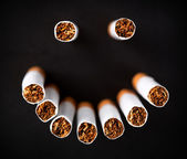 Smiley face made of cigarettes — Stock Photo