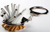 Cigarettes locked to handcuffs — Stock Photo