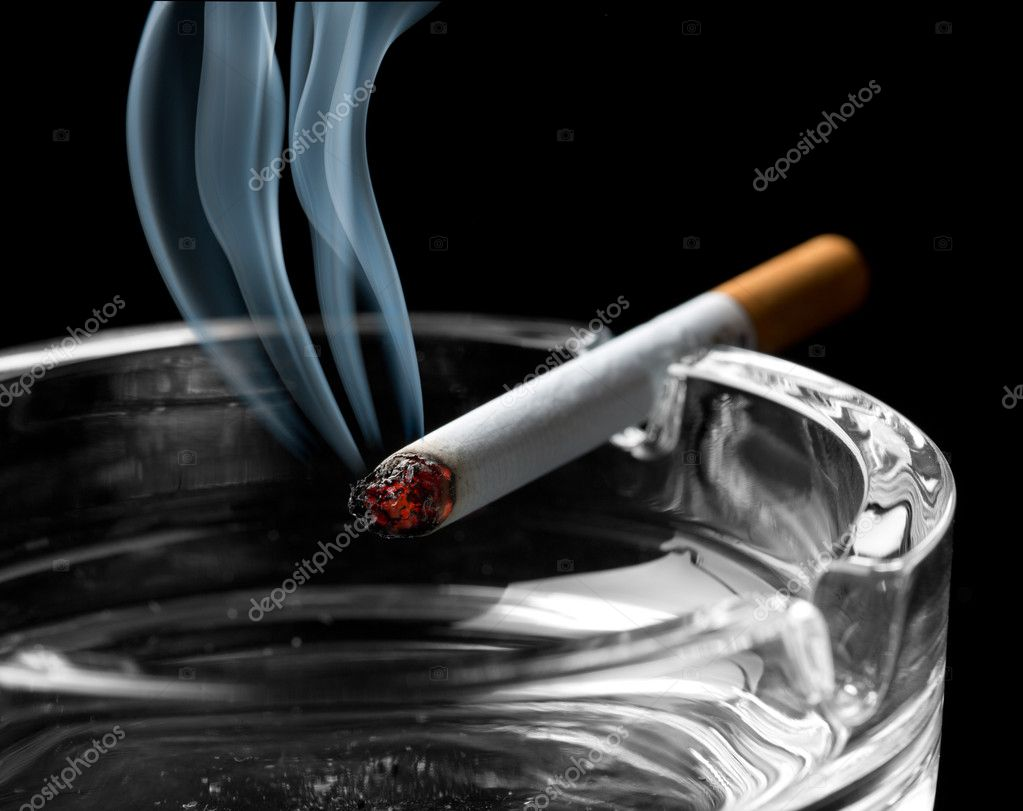 Closeup of cigarette on ashtray with a beautiful wisp of smoke — Stock Photo #12261314