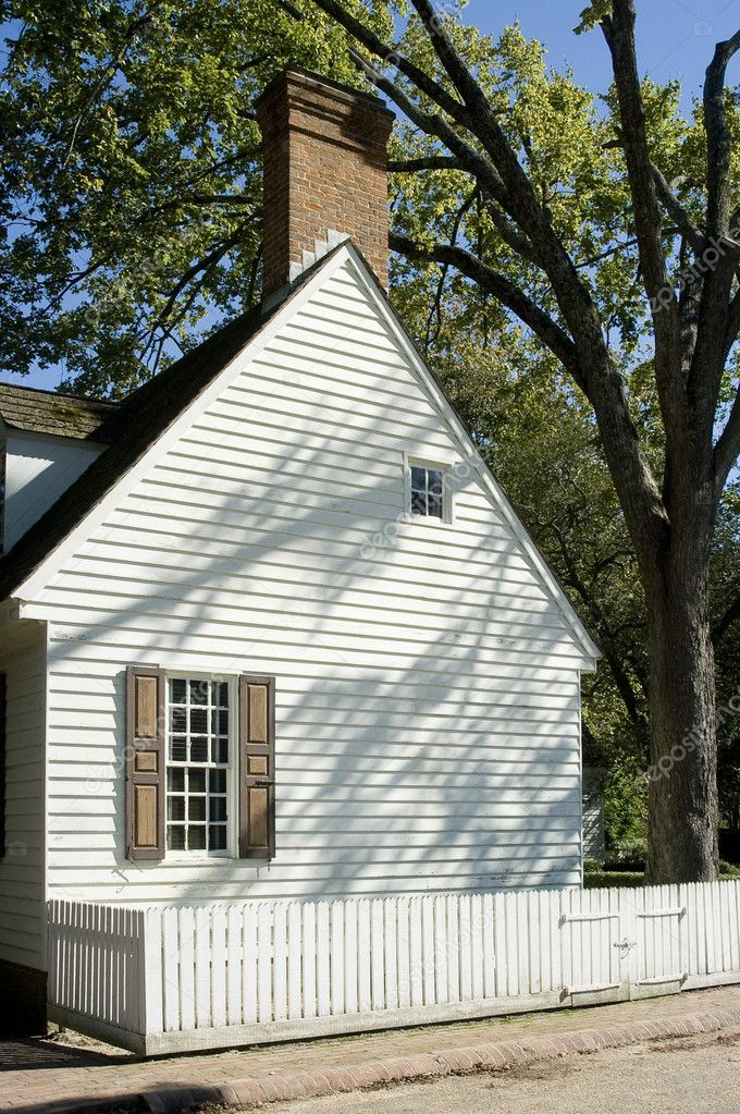 Side of white colonial house with picket fence, nice shadows from big tree — Stock Photo #12107400