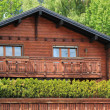 Wooden chalet among summer trees - Stock Photo