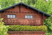 Wooden chalet among summer trees — Stock Photo