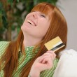 Young woman with credit card laughing — Stock Photo