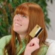 Young woman with credit card smiling — Stock Photo