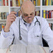 Stock Photo: Doctor looking up information on medicine