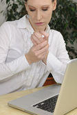 Woman with arthritis massaging hands in pain — Stockfoto