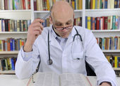 Doctor looking up information on medicine — Stock Photo