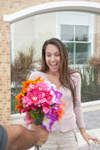 Man surprising his girlfriend with a bouquet — Stock Photo