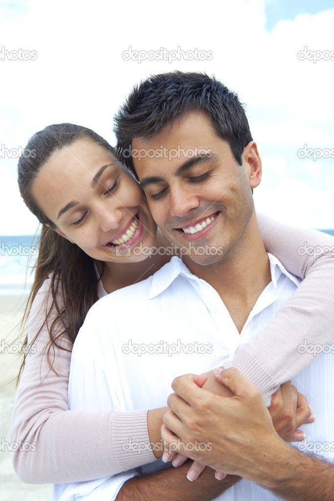 Happy couple in love daydreaming together on the beach  Stock Photo #10910843