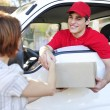 Delivery courier delivering package and handshake - Stok fotoğraf
