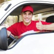 Postal delivery courier in a van showing thumb up hand sign — Stockfoto