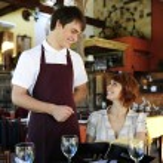 Waiter talking to costumer at the restaurant — Stock Photo