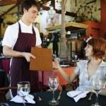 Waiter giving menu to costumer at the restaurant — Stock Photo