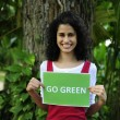 Environment conservation: woman in the forest holding a go green sign — Stock Photo #10958222