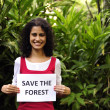 Stock Photo: Environment conservation: woman holding a save the forest sign