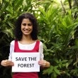 Environment conservation: woman holding a save the forest sign — Stock Photo #10958235