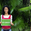 Environment conservation: woman in the forest holding a go green sign - Stock Photo