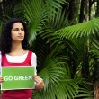 Environment conservation: woman in the forest holding a go green sign — Stock Photo #10958266