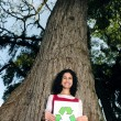 Recycling: woman in front of a tree holding a recycle sign — Stock Photo #10958518