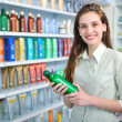 Woman at pharmacy buying shampoo - Stok fotoraf