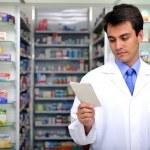 Pharmacist reading prescription at pharmacy — Stock Photo