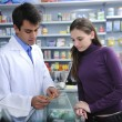 Stock Photo: Pharmacist advising client at pharmacy