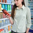 Woman at pharmacy buying shampoo — Stock Photo