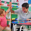 Preschool teacher and child giving high-five - Stok fotoğraf