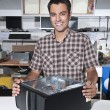 Happy owner of a computer repair store — Stock Photo