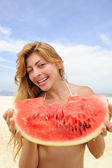 Woman eating watermelon on the beach — Stock Photo