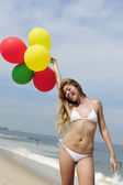 Woman holding colorful balloons on the beach — Stock Photo
