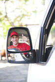 Delivery courier in van, rear view mirror — Stock Photo