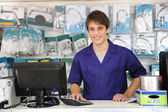 Portrait of a sales assistant behind the counter — Stock Photo