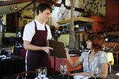 Garçom dando menu de cliente no restaurante — Fotografia Stock
